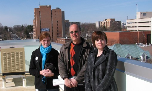 Cindy Powers, Michael Belisle, and Catriona Fraser on the PeriPoint rooftop with a view of the Bethesda cityscape.
