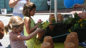 Children potted flowers at the American Plant tent.
